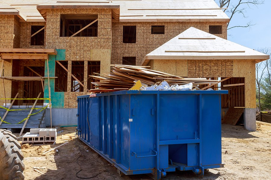 blue garbage container full of construction debris