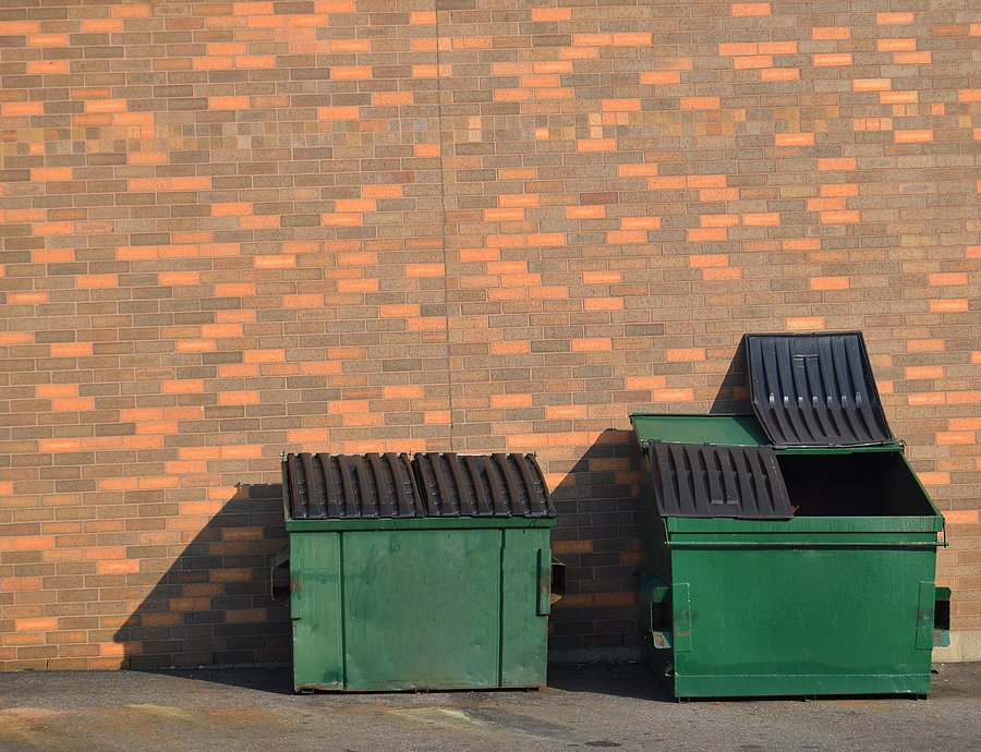 two green recycling dumpster